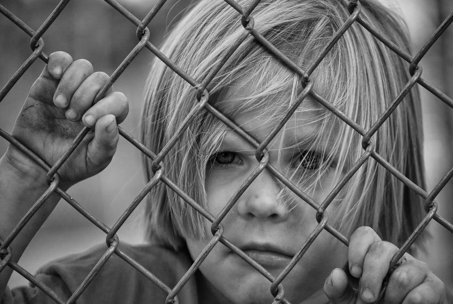 pojke står bakom staket